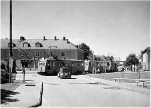 Linje 8 i korsningen Tyresövägen–Sockenvägen, 1950. DKW, liksom Volkswagen var vanliga efter kriget. Notera varning för tåg-skylten.